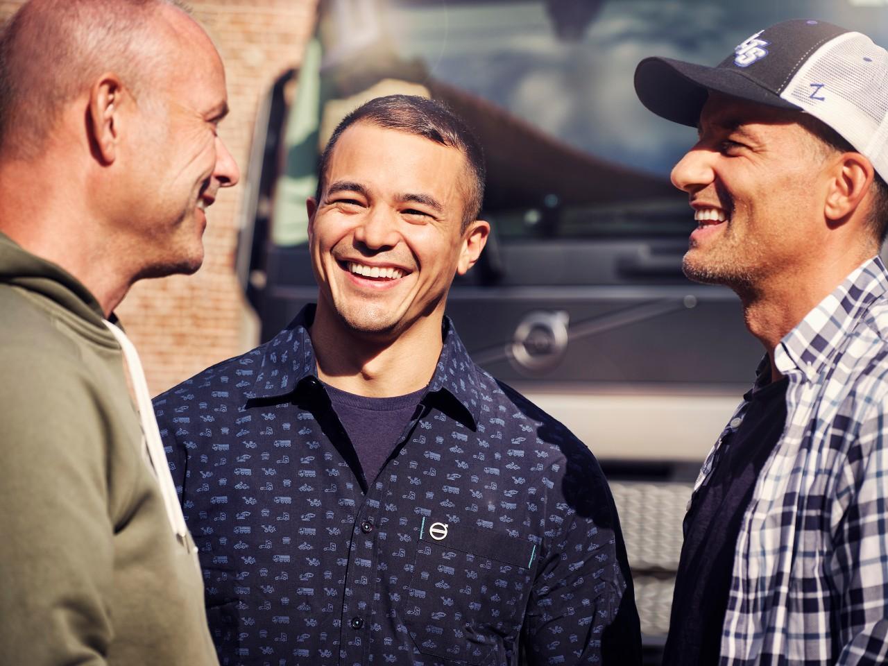 Pohľad zblízka na troch mužov usmievajúcich sa pred nákladným vozidlom Volvo