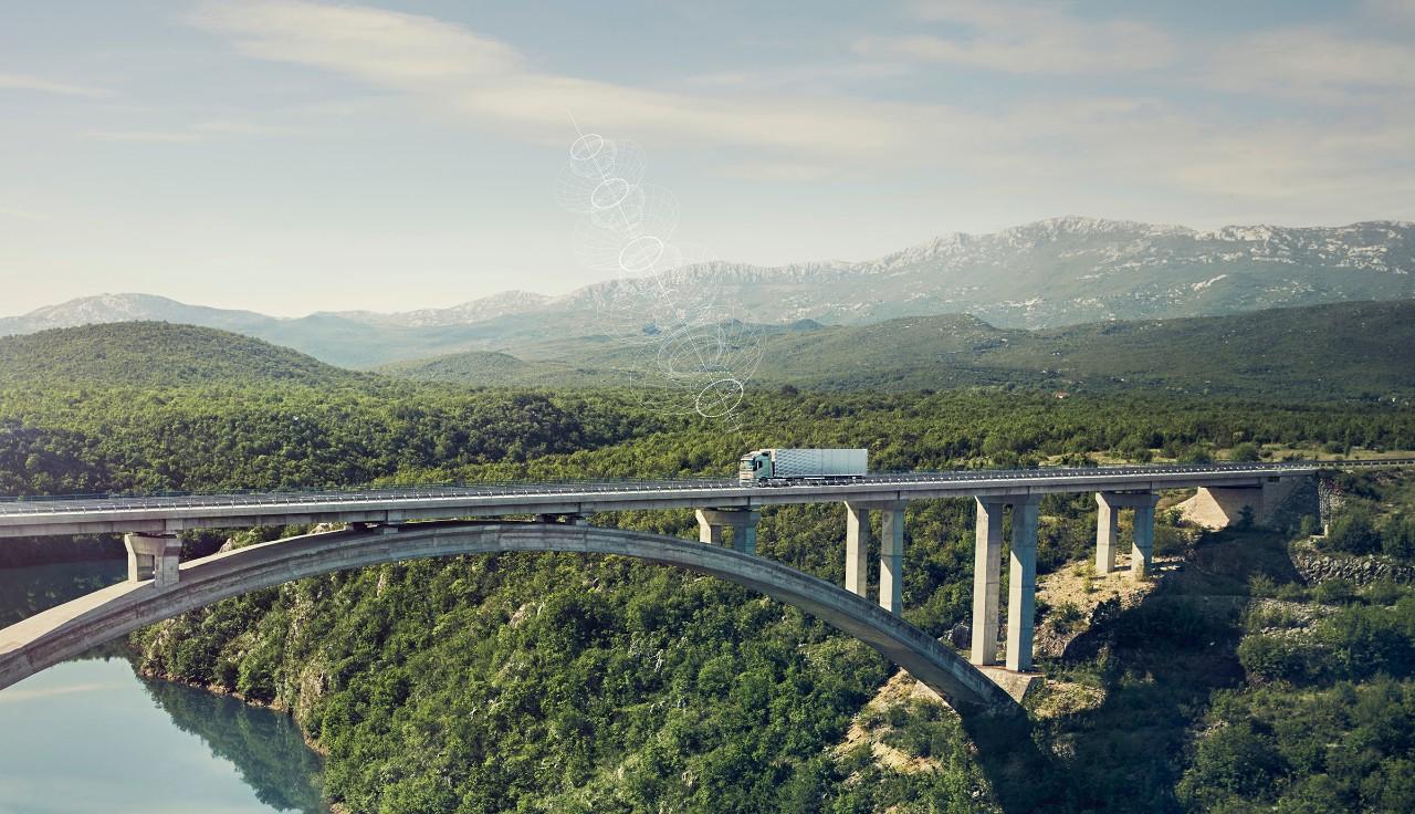 Pripojené nákladné vozidlo Volvo jazdí po moste na odľahlom mieste