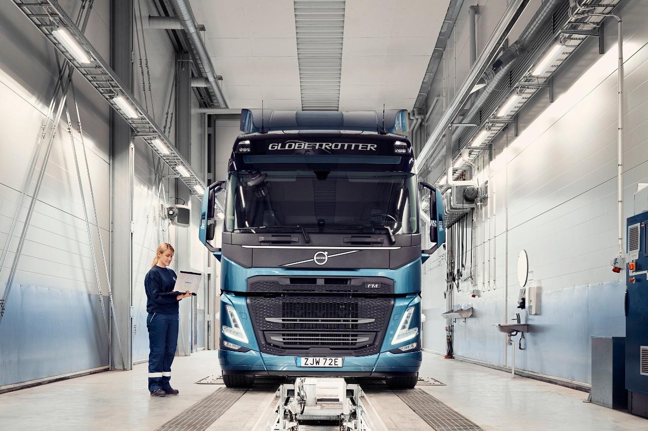 Servisný technik Volvo drží počítač, keď stojí vedľa nákladného vozidla